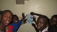 """Les jeunes du """"Hope for Children"""" accrochent une affiche dans la cuisine"""